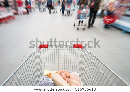 Shopping cart, trolley in a big supermarket with blurred people - stock photo