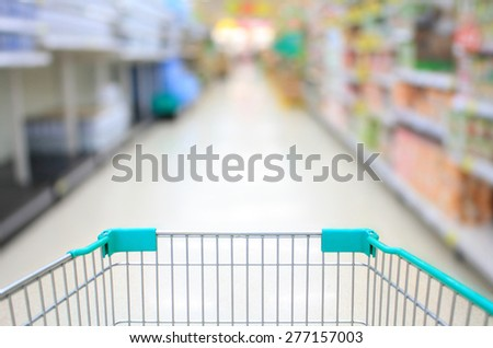 Shopping Cart View in Supermarket Aisle and Shelves defocus background - stock photo