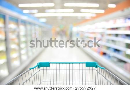Shopping Cart View in Supermarket Aisle Milk Yogurt Frozen Food Freezer and Shelves with customer defocus background - stock photo
