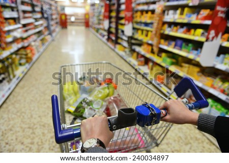 Shopping Cart View on a Supermarket Aisle and Shelves - Image Has a Shallow Depth of Field - stock photo
