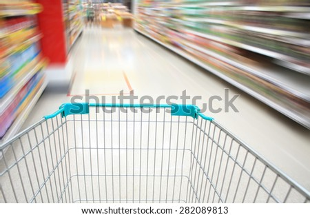 Shopping Cart View on a Supermarket Aisle and Shelves with Motion Blur - stock photo