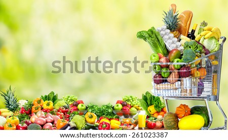 Shopping cart with vegetables over green background. Healthy diet. - stock photo