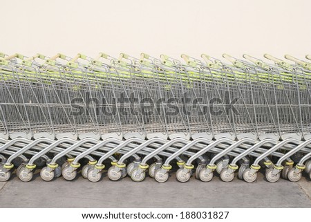 Shopping carts in a row with concrete wall background. - stock photo