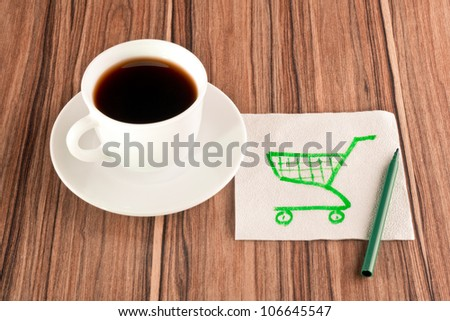 Shopping carts on a napkin and cup of coffee - stock photo