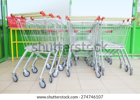 Shopping carts on car park near entrance of supermarket - stock photo
