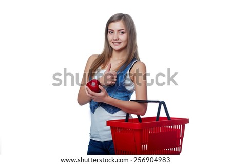 Shopping concept. Happy full length woman standing with empty red shopping basket and showing red apple, white background - stock photo