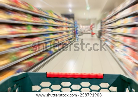 Shopping concept in supermarket for fast consumer lifestyle. Shopping cart in in blurred motion through the aisles. - stock photo