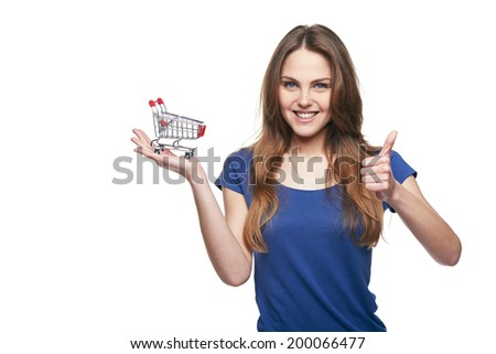 Shopping concept. Smiling happy young woman showing small empty supermarket shopping cart on her palm and gesturing thumb up, over white background - stock photo