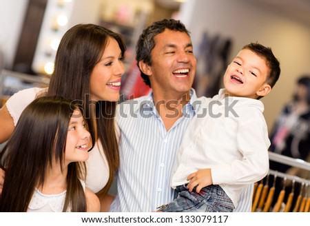 Shopping family looking very happy at a clothing store - stock photo
