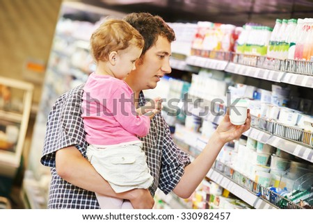 Shopping. Father man and little child girl choosing dairy products in shop supermarket - stock photo
