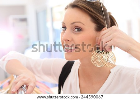 Shopping girl trying earings on in store - stock photo