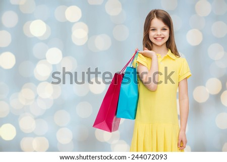 shopping, happiness and people concept - smiling little girl in yellow dress with shopping bags over holidays lights background - stock photo