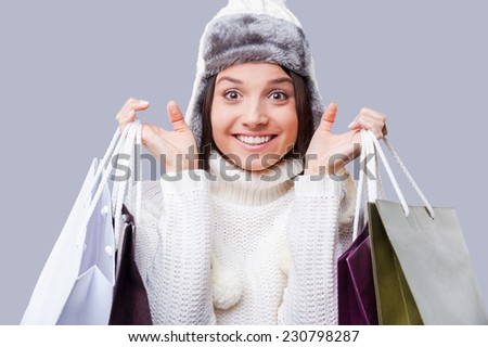 Shopping in any weather . Happy young women wearing warm winter clothing and holding packages with purchases while standing against grey background - stock photo