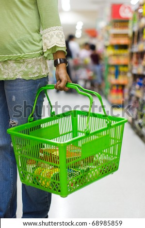 shopping in supermarket, carrying a grocery basket - stock photo