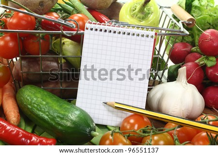 Shopping list with basket and fresh vegetables on a wooden background - stock photo