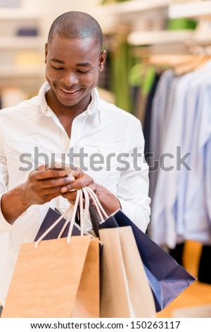 Shopping man texting on his phone at a store  - stock photo