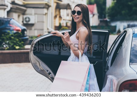 Shopping never ends. Beautiful young woman carrying shopping bags and smiling while standing near the car on the street - stock photo
