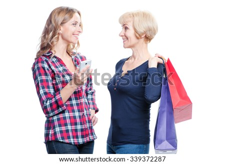 Shopping online. Pretty happy senior woman with her smiling adult daughter using smartphone. Isolated on white. - stock photo