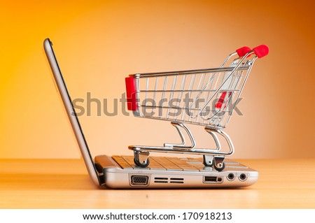 Shopping online with computer and cart - stock photo