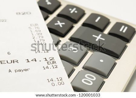 Shopping receipt on a calculator - stock photo