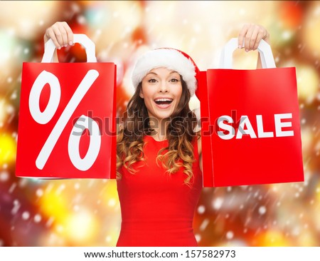 shopping, sale, gifts, christmas, x-mas concept - smiling woman in red dress and santa helper hat with shopping bags - stock photo