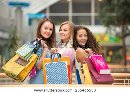 shopping, sale, happy people and tourism concept - three beautiful girls with shopping bags in mall - stock photo
