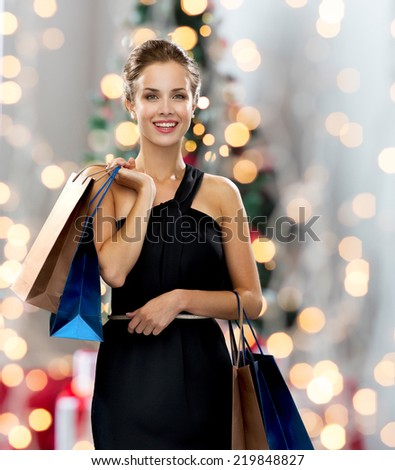 shopping, sale, people and holidays concept - smiling woman in evening dress with shopping bags over christmas tree and lights background - stock photo
