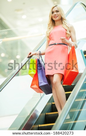 Shopping spree. Beautiful young woman standing on escalator and carrying shopping bags - stock photo
