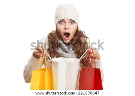 Shopping surprised woman holding bags. Winter sales. - stock photo