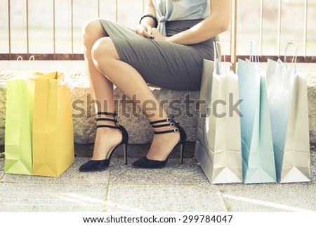 Shopping - Therapy for womankind. Unrecognizable female person sitting outside next to lots of colorful shopping bags. - stock photo