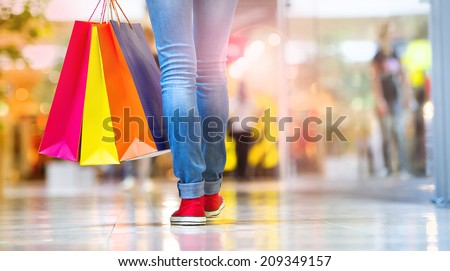 Shopping time, closeup of teenage girl legs with shopping bags at shopping mall - stock photo