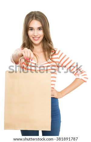 Shopping time. Portrait of a young beautiful brunette girl standing holding a shopping bag with copy space and smiling, isolated on white background - stock photo