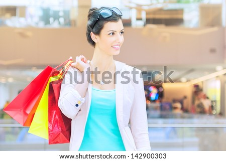 Shopping time Young woman with shopping bags at mall, looking away - stock photo