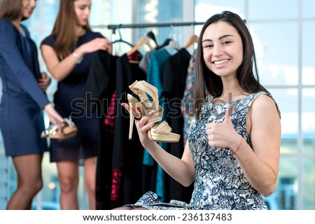 Shopping together. Happy girl holding barefoot persons in his hands and looking directly into the camera showing a thumbs up while her friend choose the dress on a hanger. - stock photo