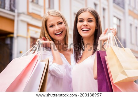 Shopping together is fun. Two attractive young women holding shopping bags and smiling while standing outdoors - stock photo