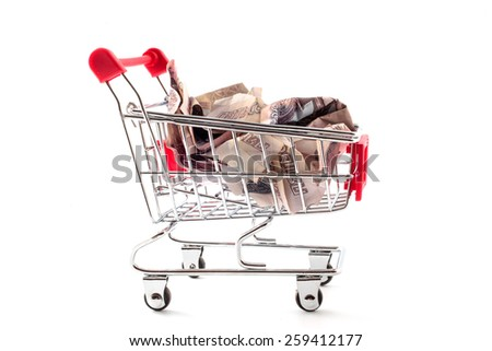 shopping trolley with crumpled ruble banknotes - stock photo