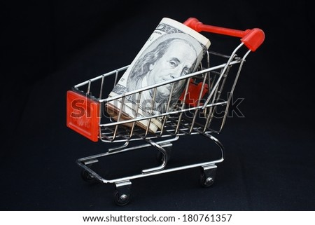 Shopping trolley with dollars on black background - shopping car - stock photo