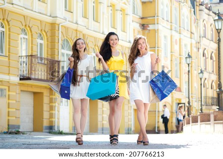 Shopping weekend. Three attractive young girl holding shopping bags while walking on the street laughing and smiling. Girls full length - stock photo