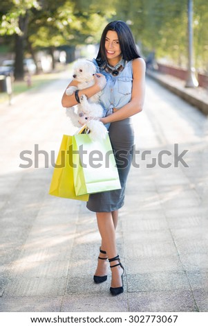 Shopping with my doggy. Fashionable young woman holding a Maltese dog in her arms and carrying a lots of colorful shopping bags. - stock photo