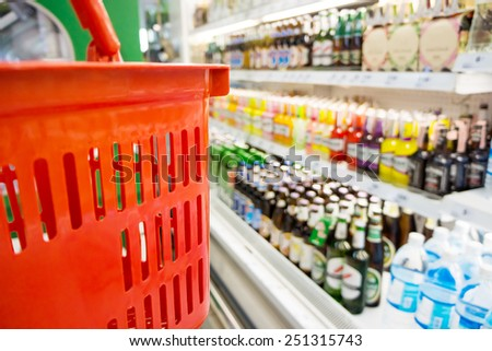 Shopping with red plastic basket in supermarket - stock photo