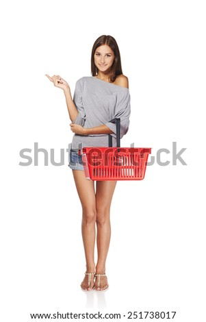 Shopping woman. Full length excited casual young woman with empty shopping cart basket pointing finger at blank copy space, over white background - stock photo