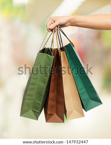 shopping - woman hand holding shopping bags in shopping center - stock photo