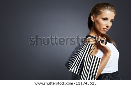 Shopping woman holding bags, isolated on gray studio background. - stock photo