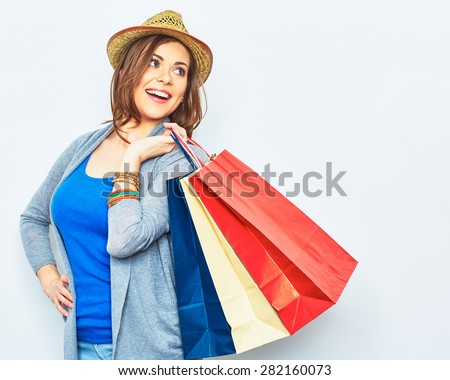 shopping woman holding bags, looking behind. sensual female model smiling. yellow hat. - stock photo