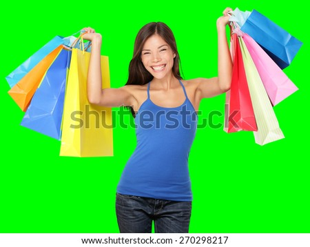 Shopping woman holding shopping bags above her head smiling happy during sale shopping spree. Beautiful young female shopper isolated on green background. - stock photo
