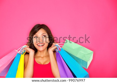 Shopping woman holding shopping bags looking up to the side on pink background at copy space. Beautiful young mixed race Caucasian / Chinese Asian shopper smiling happy. - stock photo
