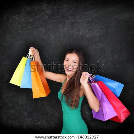 Shopping woman holding shopping bags on blackboard background with copy space for your text or design. Happy excited female shopper showing purchases excited and joyful. Mixed race Asian girl - stock photo
