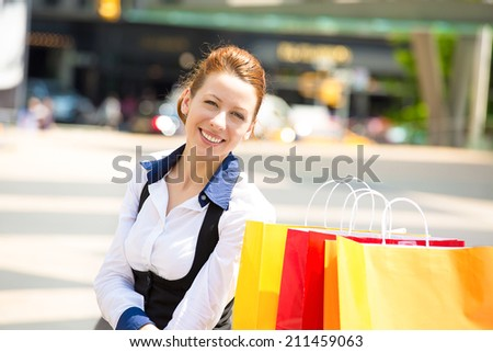 Shopping woman in New York City. Beautiful happy, smiling summer shopper with yellow shopping bags relaxing on sunny day outside. Positive emotions, face expression. Caucasian model in Manhattan, USA. - stock photo