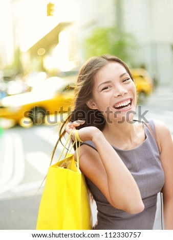 Shopping woman on Manhattan, New York City smiling happy excited walking holding shopping bags with yellow taxi cab in background. Beautiful young multi-racial female shopper laughing joyful outside. - stock photo