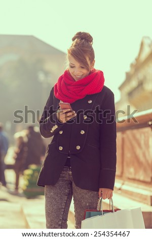 Shopping woman sending a text message on her cell phone. Soft focus. - stock photo